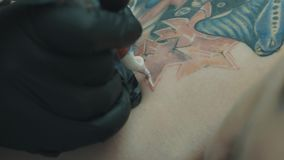 Tattooist que hace un tatuaje en la parte posterior del ` s de la muchacha almacen de video