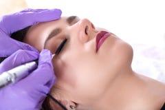 Tattooist robi eyeliner z stałym elementem uzupełniał na pięknej młodej dziewczynie obraz stock