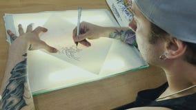 Tattooist trekt de schets op het vindende document op het glas met licht stock footage