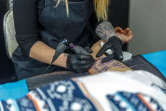A tattooist woman draws with the tattoo machine, the outline of Stock Image