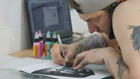 Tattooistbesprekingen op de telefoon en het opnieuw tekenen van de schets met carbonpapier stock video