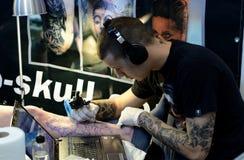 Tattooisten gör en tatuering på hans klient på 18 April, 2015, Sofia, Bulgarien Arkivbild