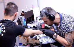 Tattooisten gör en tatuering på hans klient på 18 April, 2015, Sofia, Bulgarien Royaltyfria Foton