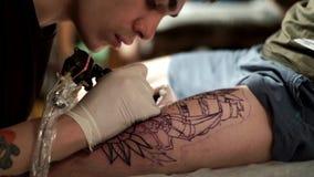 Tattooisten tatuerar en klient med en tatueringmaskin arkivfilmer