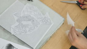 The tattoooist cuts with scissors a tracing paper with sketch stock video
