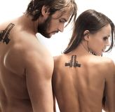 Tattoos. Beautiful couple turned away with tattoos on the back Stock Photography