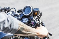 Tattoos on arms of motorcycle rider on custom made scrambler sty Stock Image