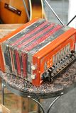 Tatty orange `Tivoli` accordion on a flea market stall royalty free stock image