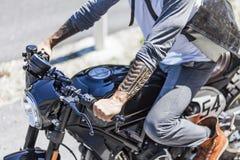 Tatuaże na rękach motocyklu jeździec na na zamówienie scrambler sty Zdjęcia Stock