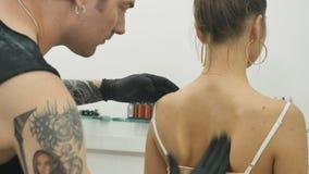 Tatuażu artysta dezynfekuje dziewczyny ` s skórę z antyseptykiem przed stosować tatuaż zdjęcie wideo
