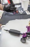 Tatuażu artysta refilling pióro od colour atramentów nalewał w małego c Zdjęcie Royalty Free