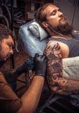 Tatuaggio di lavoro dello specialista del tatuaggio nello studio del tatuaggio Fotografia Stock
