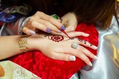 Tatuaggio di progettazione del hennè Donne che applicano il tatuaggio del hennè dei fiori sulle mani delle donne Artista che appl immagine stock libera da diritti