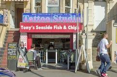 Tatuaggio e chip, spiaggia britannica Immagini Stock