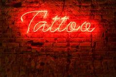 Tatuaje de neón rojo de la palabra del letrero que brilla intensamente Imagenes de archivo