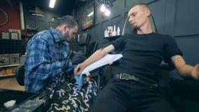 Tatuando di un uomo con una mano artificiale stock footage