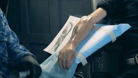 Tatuera av en syntetisk hand som utförs av den manliga konstnären stock video