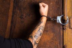 Tatuerad hand av en handfängslad brottsling royaltyfri fotografi
