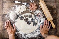 Tatuerad kock` s räcker matlagningryssklimpar på trätabellen royaltyfri fotografi