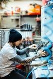 Tatuerad mekaniker Checking Engine Part Royaltyfria Foton