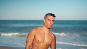 Tatuerad sexig manlig lagledare för kroppsbyggare på stranden stock video