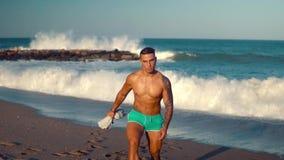 Tatuerad sexig manlig lagledare för kroppsbyggare på stranden arkivfilmer