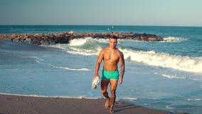 Tatuerad sexig manlig lagledare för kroppsbyggare på stranden lager videofilmer