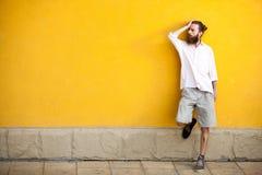 Tatuerad skäggig hipster för mode på den gula väggen royaltyfri foto