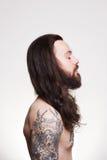 Tatuerad stilig skäggig man med långt hår arkivbild
