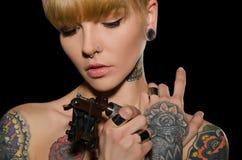 Tatuerad ung kvinna med tatueringmaskinen Fotografering för Bildbyråer
