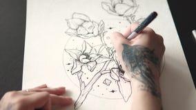 Tatueringförlagen gör en skissa av tatuering på papper stock video
