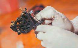 tatueringkonstnär i rubber vita handskar som får klara att göra en tatuering i salongen Royaltyfri Fotografi