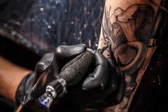 Tatueringkonstnären gör en tatuering arkivfoton