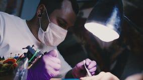 Tatueringkonstnären gör tatueringen stock video