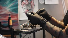 Tatueringkonstnären samlar tatueringmaskinen flickatatueringförlagen förbereder en roterande tatueringmaskingevär för att dra en  arkivfilmer