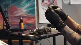 Tatueringkonstnären samlar tatueringmaskinen flickatatueringförlagen förbereder en roterande tatueringmaskingevär för att dra en  lager videofilmer