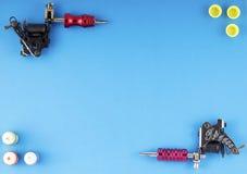 Tatueringmaskiner med tre flaskor av färgpulver och tre färgpulverbehållare på blå bakgrund Arkivfoton