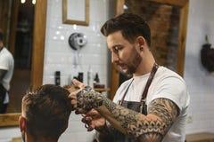 Tatuujący fryzjer męski daje ostrzyżeniu Zdjęcie Stock