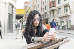 Tatuujący kobiety obsiadanie na ławce i używać mądrze telefon w ulicie Fotografia Royalty Free