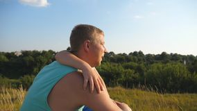 Taty i dziecka obsiadanie przy zieloną trawą na wzgórzu i patrzeć piękna natura ich naprzód Ojciec z jego małym zdjęcie wideo