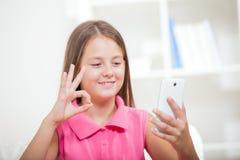 Taubes Mädchen, das unter Verwendung der Gebärdensprache auf dem Nocken des Smartphones spricht stockfotografie