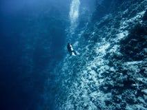 Taucher steigt tief in das Meer ein lizenzfreies stockfoto