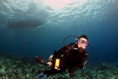 Taucherschwimmen unter dem Boot lizenzfreie stockbilder