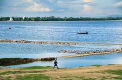 Taungthaman Lake and boatman in Amarapura with pagodas in the background Stock Images