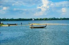 Taungthamanmeer en boatman in Amarapura met pagoden op de achtergrond Stock Afbeeldingen