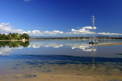 Tauranga Harbour, NZ. Tauranga Harbour on a still day with mirror reflection of a pylon and clouds in the water stock photo