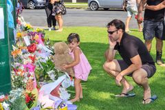 Young girl lays a teddy bear with memorial flowers. Tauranga, New Zealand - March 16 2019: A little girl places a large teddy bear with floral tributes laid royalty free stock image