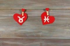 Tauro y pescados muestras del zodiaco y del corazón Backgroun de madera Fotos de archivo libres de regalías