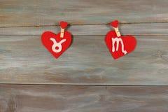 Taurus i skorpion znaki zodiak i serce felted Drewniany obraz royalty free
