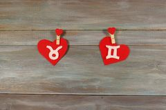 Taurus and twins. signs of the zodiac and heart. wooden backgrou stock images